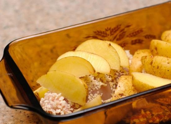 Xếp các cuộn thịt gà vào khay và cho khoai tây lên