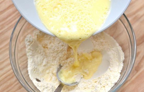 Đổ bát trứng sữa vào bát hỗn hợp bột
