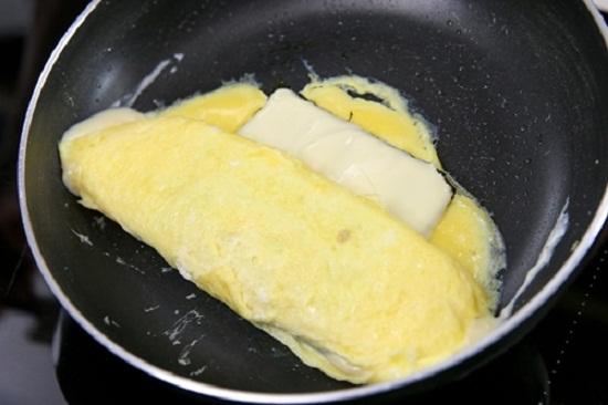 Khi phô mai bắt đầu chảy ra thì dùng đũa cuộn trứng lại