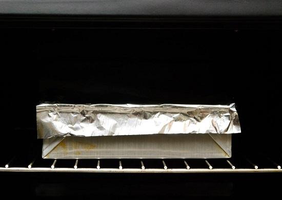 phủ một tấm giấy bạc lên miệng khay  và nướng thịt