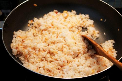 Đun nóng dầu ăn trong chảo, cho trứng và cơm vào đảo nhanh