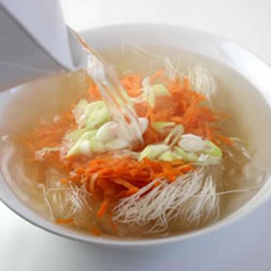 Đổ nước sôi vào ngâm  bún gạo, cà rốt và đầu hành