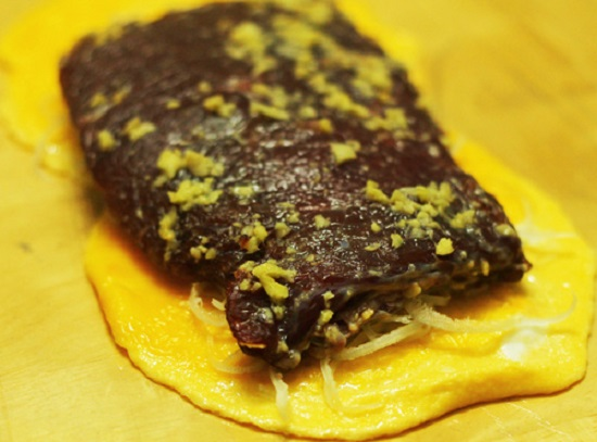 Trải một lớp giấy gói thực phẩm đến một miếng trứng, một lớp bì, rồi cuối cùng tới thịt bò