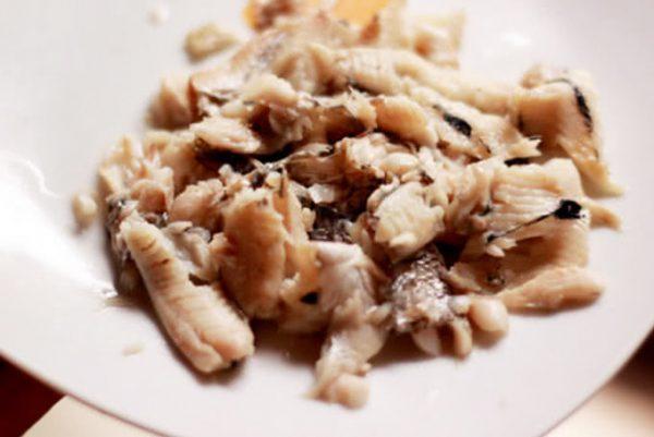 Gỡ thịt cá rô ướp cùng gia vị