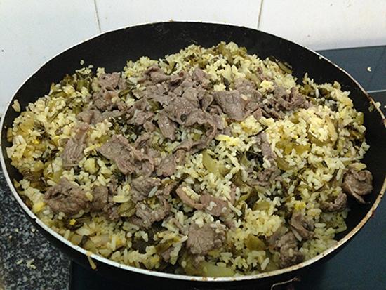 Cho bát thịt bò và dưa cải vào chảo cơm nêm nếm lại gia vị vừa ăn