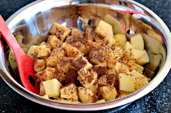 Cho táo vào một bát tô lớn rắc đều bột cacao vào