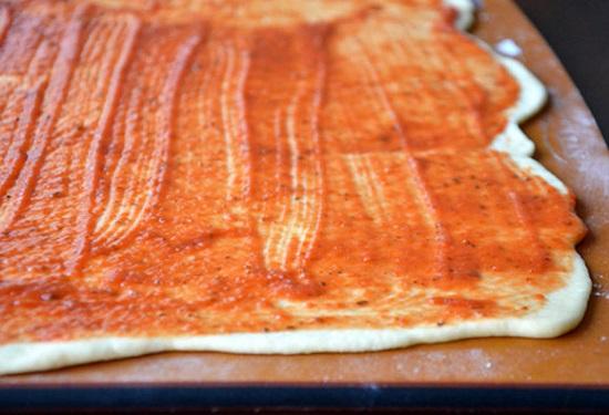 Cán bột thành một hình chữ nhật rồi phủ một lớp sốt cà chua lên mặt bánh