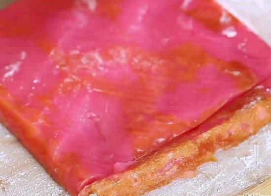 Rắc bột năng lên mặt bàn rồi úp mặt trên của bánh xuống bàn