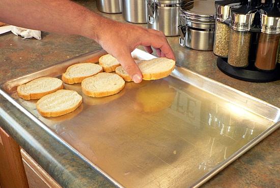 Đổ một ít dầu oliu lên khay nướng rồi đặt các lát bánh mì lên