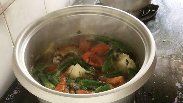 Cho đậu bắp và cà chua vào, nêm nếm lại cho vừa ăn