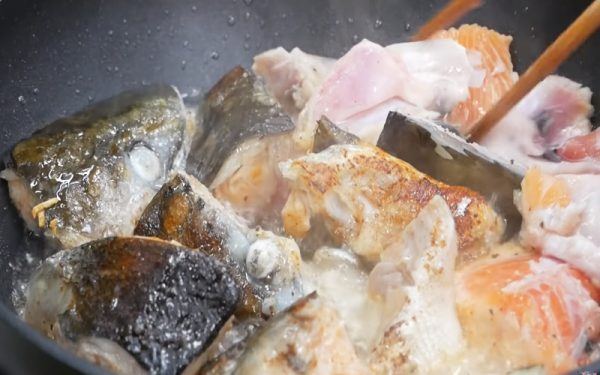 Phi thơm tỏi và sả rồi cho đầu cá hồi vào chiên qua