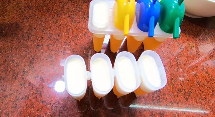 Đổ hỗn hợp sữa vào khuôn kem cam rồi cho vào tủ lạnh cho đông lại