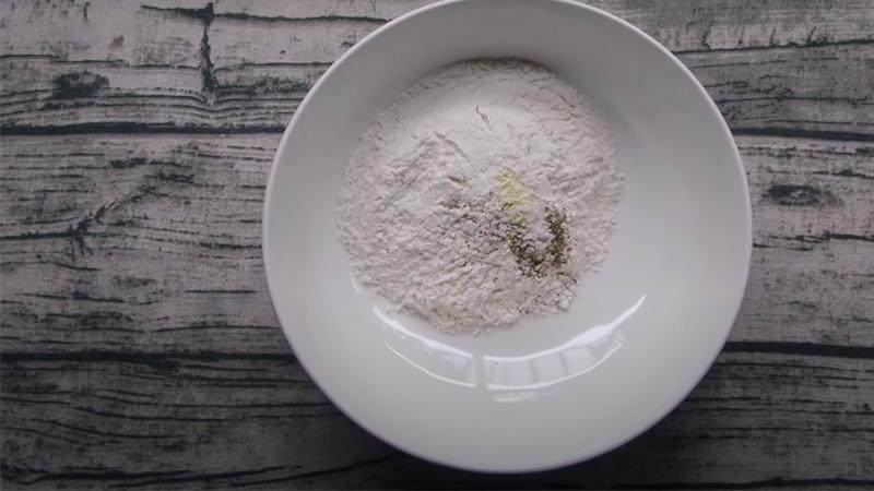 Cho bột mì cùng các loại gia vị vào tô trộn đều
